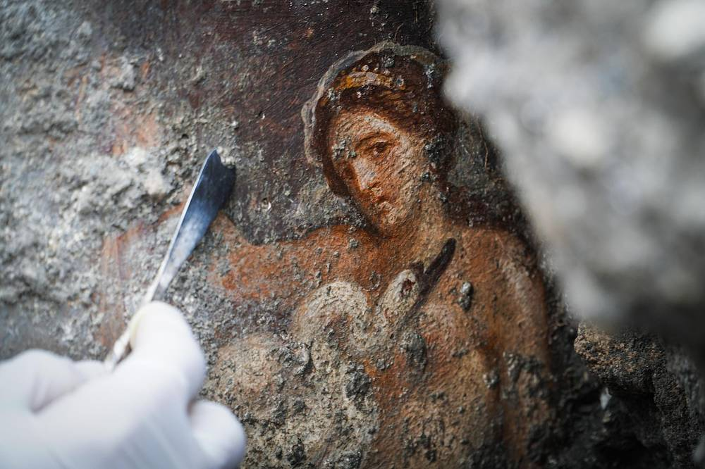 An archelogist works on the fresco ''Leda e il cigno'' (Leda and the swan) recently discovered in the Regio V archeological area in Pompeii, Italy, November 19