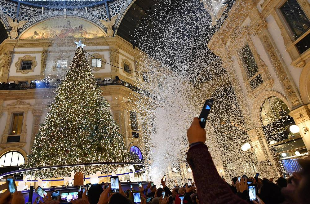 People take pictures during the lighting ceremony of the Christmas illuminations and Swarovski Christmas Tree in Milan, Italy