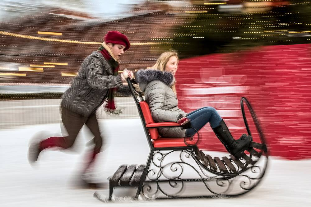 People riding a sleigh as part of the Journey to Christmas winter festival in Moscow