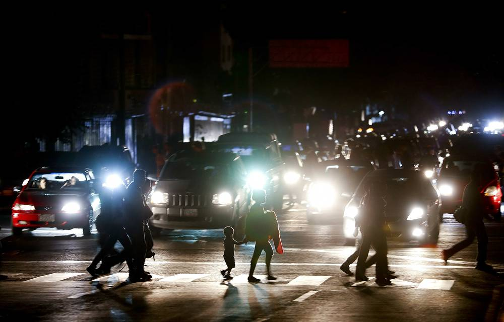 Residents cross a street in the dark after a power outage in Caracas, Venezuela
