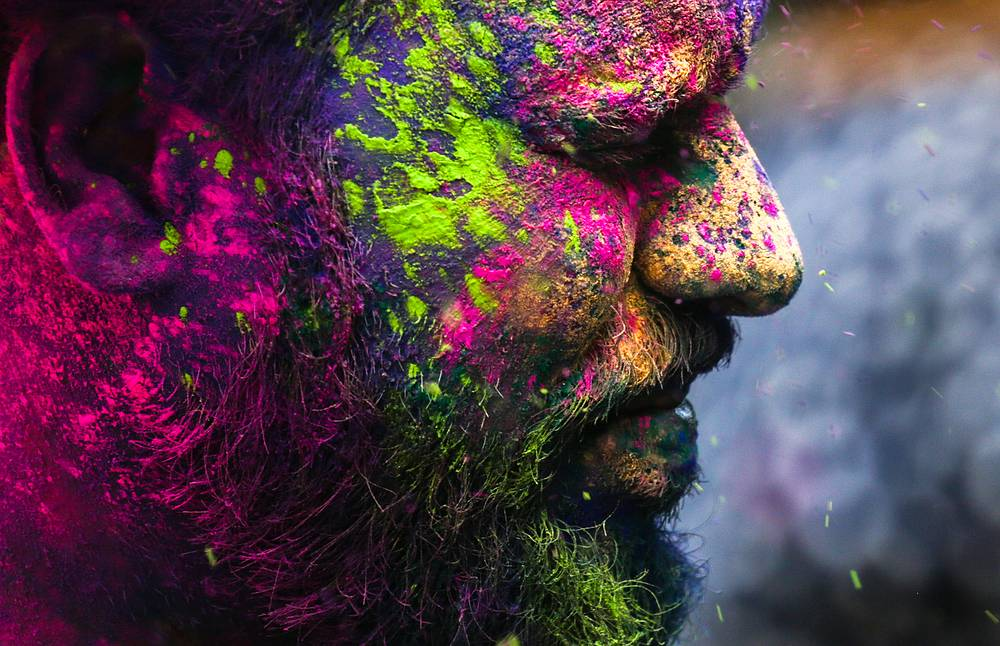 An Indian reveller covered with powdered colors celebrates the Holi festival in Mumbai