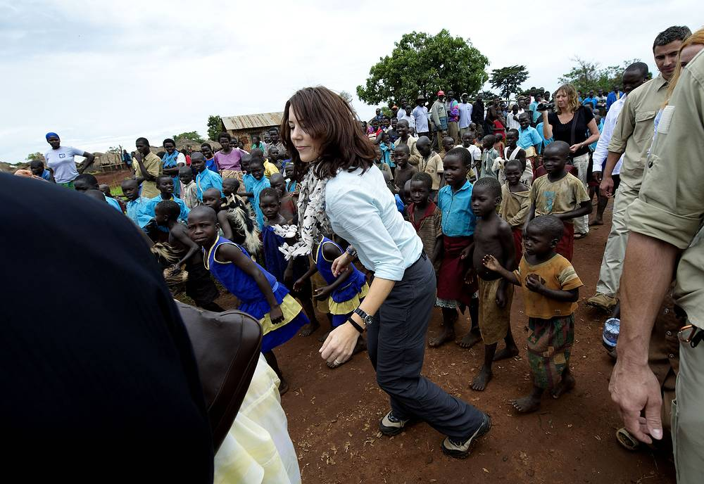 Danish Crown Princess Mary dancing with children outside a school in the Ongako IDP camp near Gulu in Uganda, 2008
