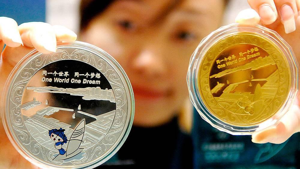 Памятные монеты, выпущенные Народным банком Китая к летним Олимпийским играм 2008 в Пекине. Фото AP Photo/Xinhua, Zhao Jing
