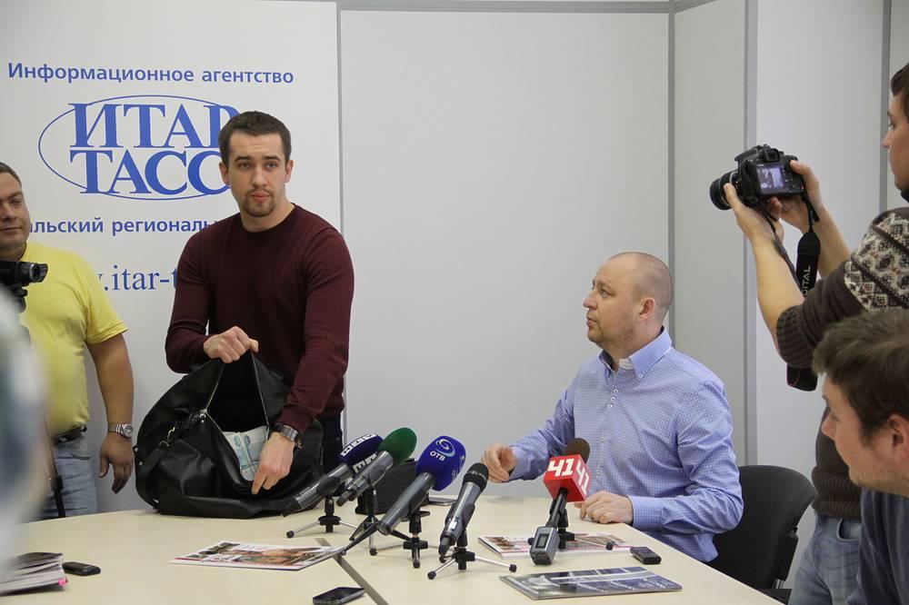 Один из организаторов боя Алексей Титов демонстрирует часть собранных призовых денег - пять миллионов рублей