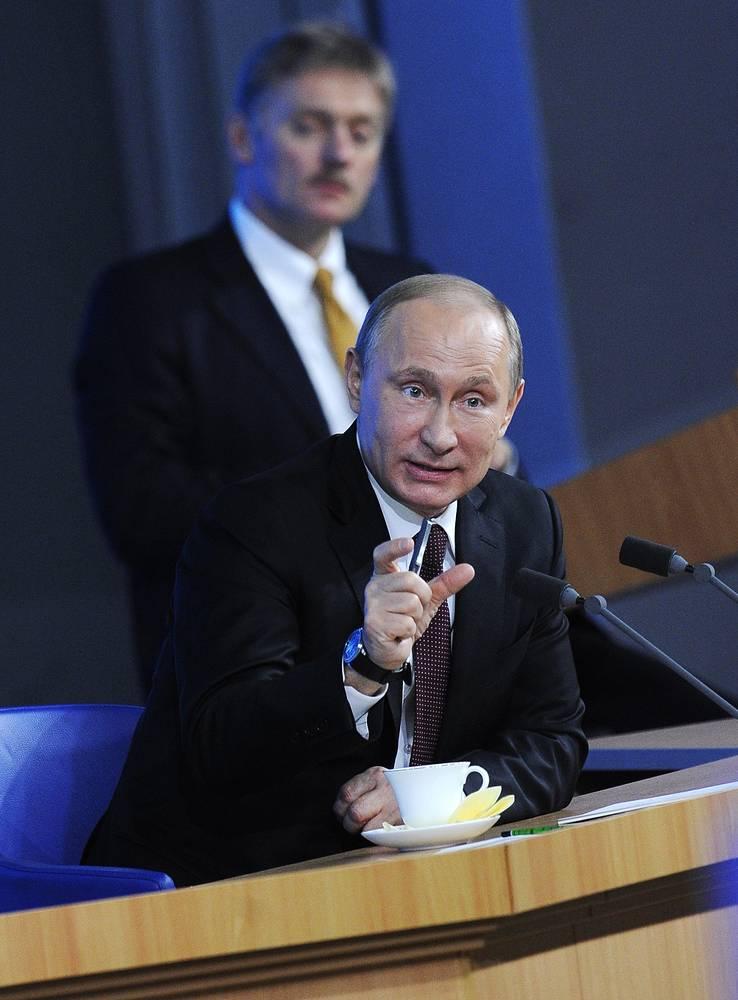 Президент России Владимир Путин (на первом плане) и пресс-секретарь президента РФ Дмитрий Песков (на втором плане) во время пресс-конференции