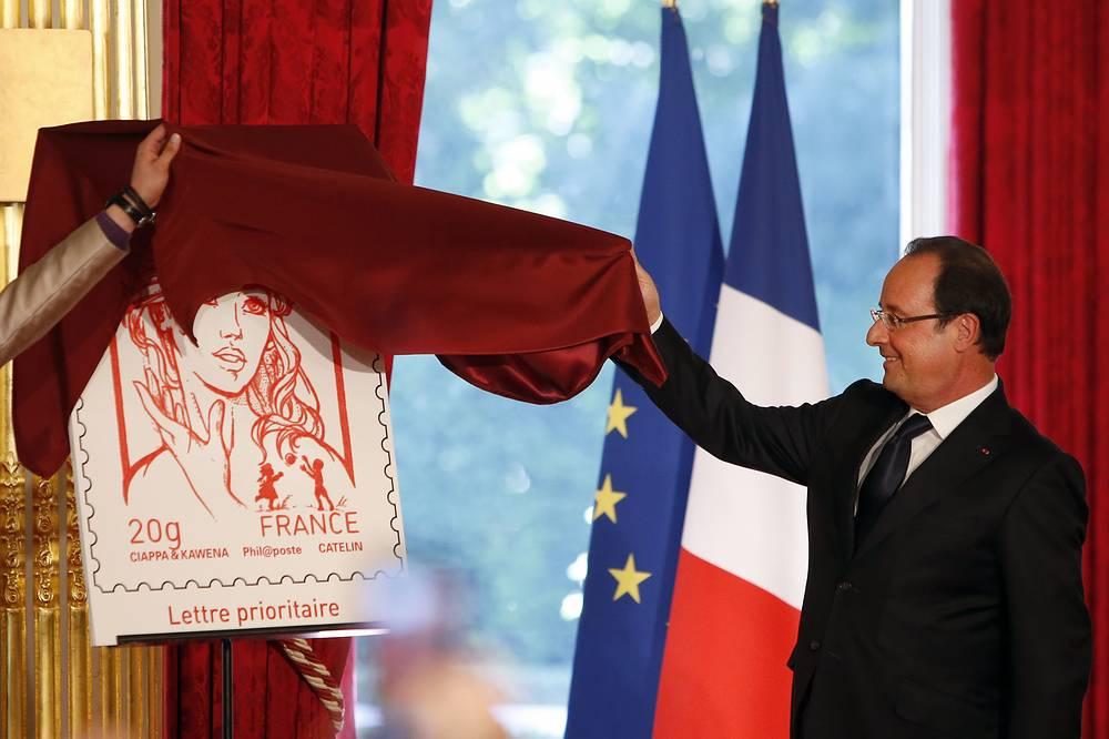 Елисейский дворец во время празднования Дня взятия Бастилии в Париже. Франсуа Олланд представляет почтовую марку с новым официальным лицом Марианны