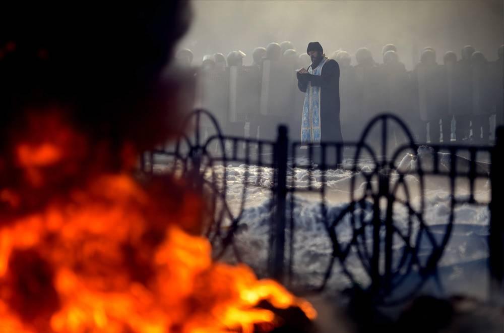 Священник читает молитву во время акций протеста на улице Грушевского в Киеве