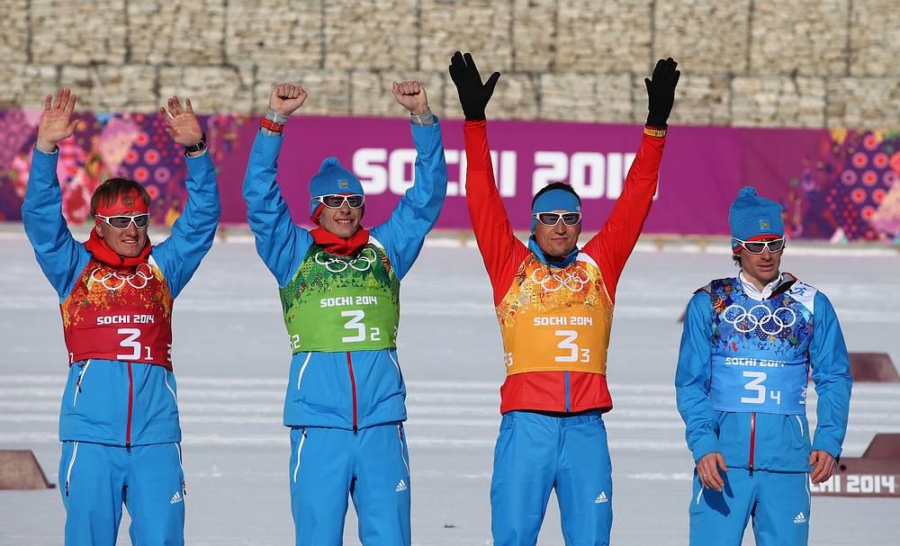 Дмитрий Япаров, Александр Бессмертных, Александр Легков и Максим Вылегжанин (слева направо), завоевавшие серебряную медаль во время цветочной церемонии