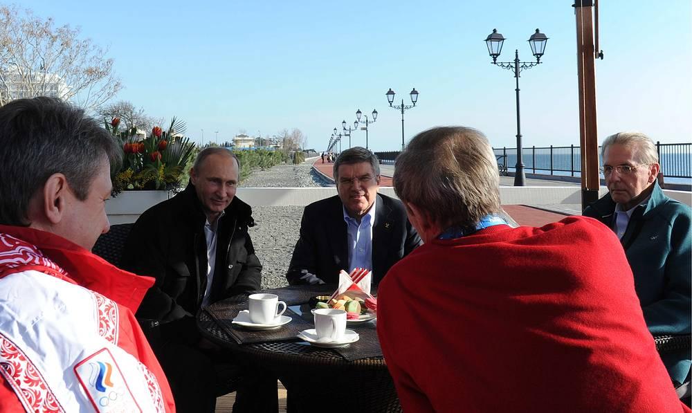 Президент России Владимир Путин, президент МОК Томас Бах и почетный президент МОК Жак Рогге (слева направо на втором плане) во время прогулки по городской набережной