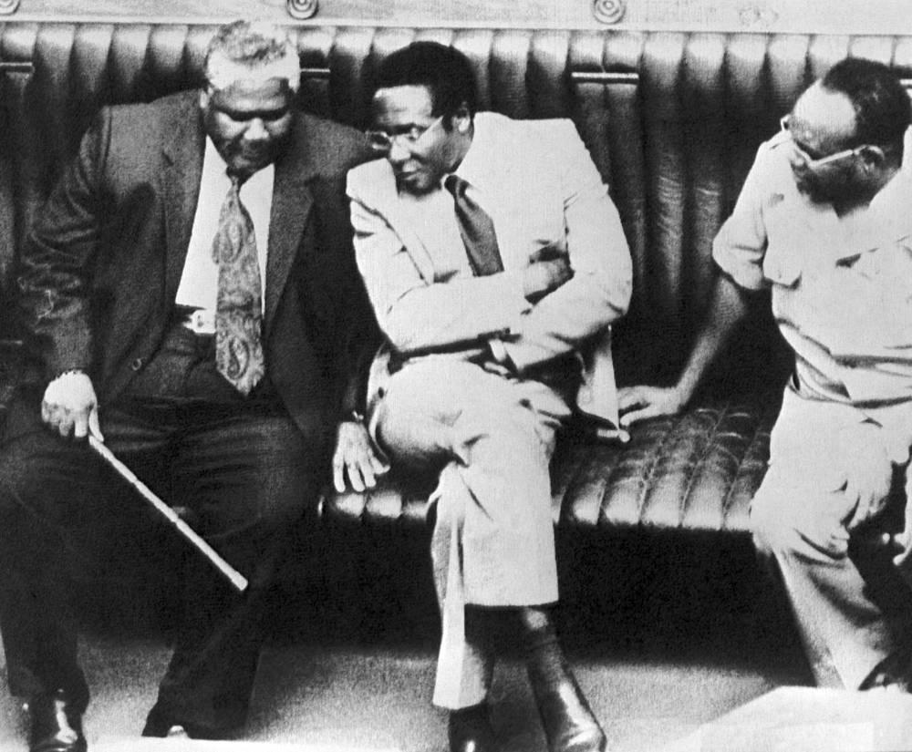 """Вскоре в отношениях между двумя партиями возникла напряжённость. Мугабе обвинил Нкомо в заговоре с целью захвата власти. Нкомо бежал из страны, его сторонники подняли восстание. В ходе операции """"Гукурахунди"""" было убито несколько десятков тысяч мирных жителей. Впоследствии Мугабе помиловал Нкомо и разрешил ему вернуться в страну при условии слияния его партии ЗАПУ с правящей ЗАНУ. Так Зимбабве превратилось в однопартийное государство. На фото: Министр внутренних дел Джошуа Нкомо, премьер-министр Роберт Мугабе и министр иностранных дел Саймон Музенда (слева направо) в 1980 году"""