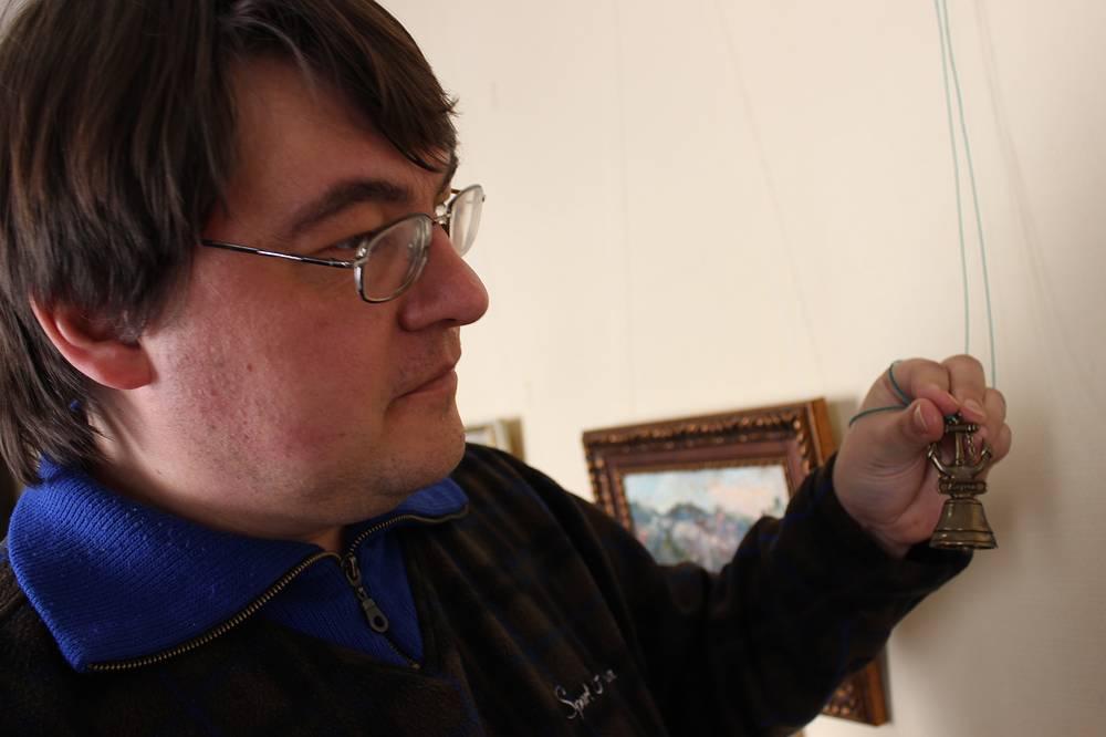 Куратор выставки Евгений Иванов с сувениром из Керчи
