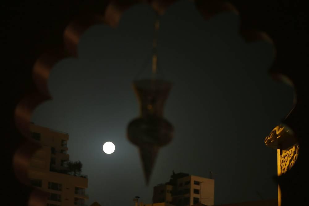 Луна на фоне здания, украшенного по случаю Рамадана, в Бейруте, Ливан
