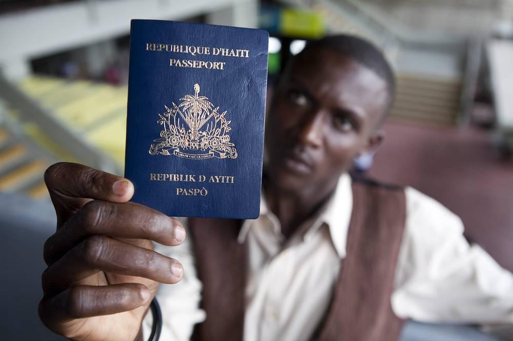 Мигрант из Гаити показывает свой паспорт после подачи документов на гражданство Доминиканской Республики. В мае 2014 года правительство Доминиканы приняло закон о правах мигрантов из Гаити