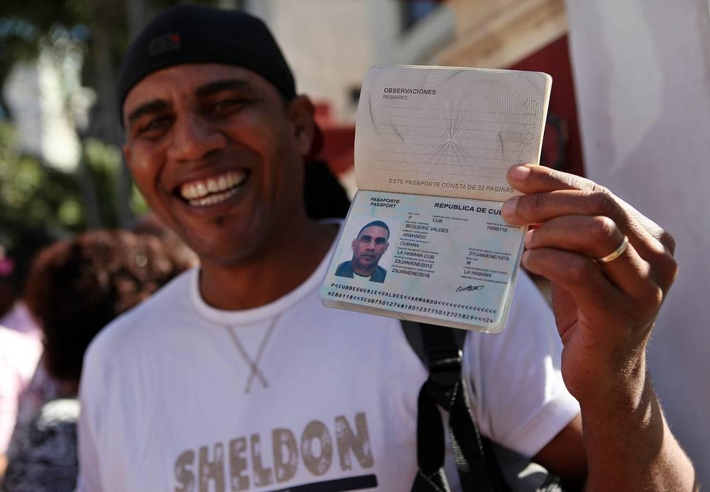 Гражданин Кубы показывает свой паспорт. В 2013 году в стране вступил в силу закон, отменяющий обязательное разрешение властей на выезд за границу и продляющий разрешенный срок пребывания за рубежом до 2 лет