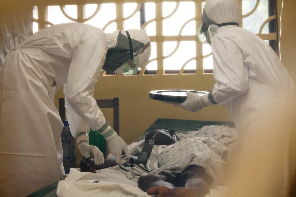 По данным ВОЗ, с 1976 года в странах Африки от геморрагической лихорадки Эбола скончались 1648 человек. На фото: медики с пациентом, зараженным вирусом Эбола, в госпитале в Либерии, 2014 год