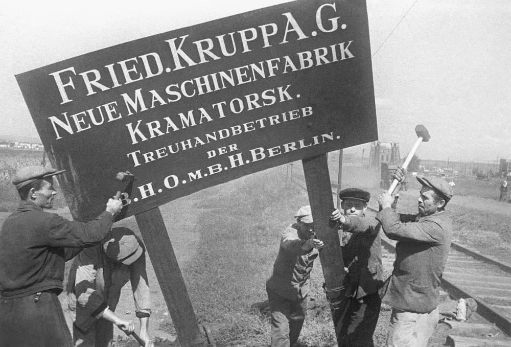 Рабочие Краматорского машиностроительного завода срывают с заводского здания вывески германского промышленника Круппа в освобожденном Донбассе, 1943 год