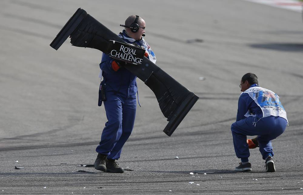 Работники убирают обломки болида с трассы