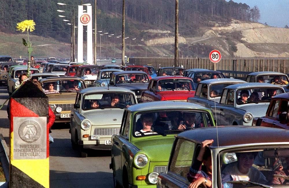 Пограничники под натиском огромного количества людей были вынуждены открыть переходы через КПП, не дожидаясь официального уведомления властей. На фото: автомобили из ГДР пересекают границу с Западным Берлином в районе Херлесхаузен, 1989 год