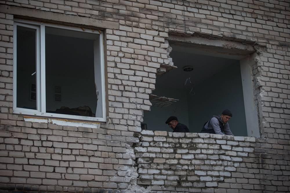 """По данным ООН, опубликованным 14 ноября, с момента начала конфликта на востоке Украины по меньшей мере 4132 человека были убиты (с учетом 298 человек, летевших рейсом MH17 """"Малайзийских авиалиний"""") и 9747 были ранены. На фото: подвергшийся обстрелу жилой дом в Первомайске Луганской области"""