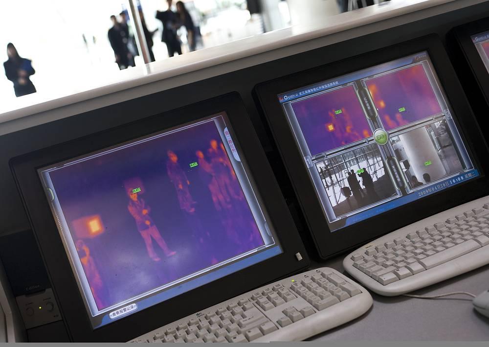 Тепловые детекторы в аэропортах используют в период возникновения эпидемий. Прибор регистрирует температуру каждого пассажира, международный аэропорт Шоуду, Пекин