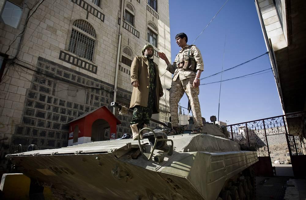 19 января в столице Йемена Сане шиитские мятежники (хоуситы) начали осаду президентского дворца. После захвата резиденции главе государства и лидерам протестующих удалось прийти к соглашению, одним из пунктов которого стало разрешение хоуситам занимать места в правительстве. Президент Йемена Абд-Раббу Мансур Хади и кабмин во главе с Халидом Махфузом Бахахом подали прошения об отставке, однако парламент страны ее не принял. На фото: один из шиитских мятежников около президентского дворца в Сане