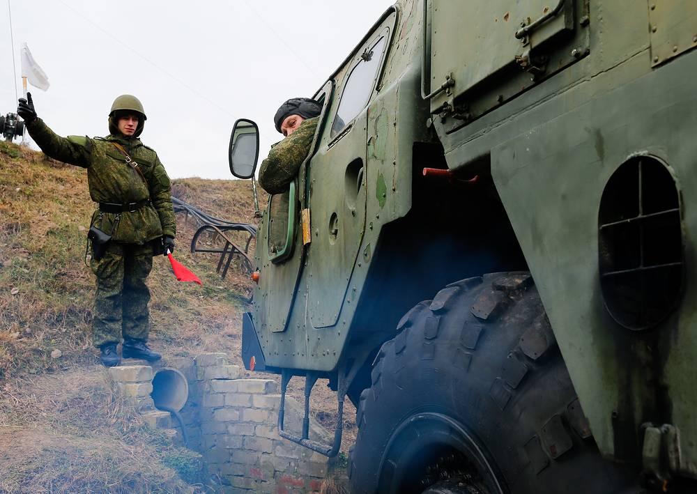 """Механик-водитель транспортной машины ЗРК С-300 маневрирует при заезде в капонир. На заднем плане -  регулировщик подает сигнал """"Внимание""""."""