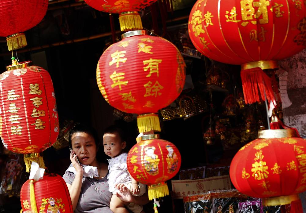 Дом украшают маленькими красными фонариками, предназначенными для отпугивания злых духов и привлечения богатства и благополучия. На фото: новогодние украшения на одной из улиц Бангкока