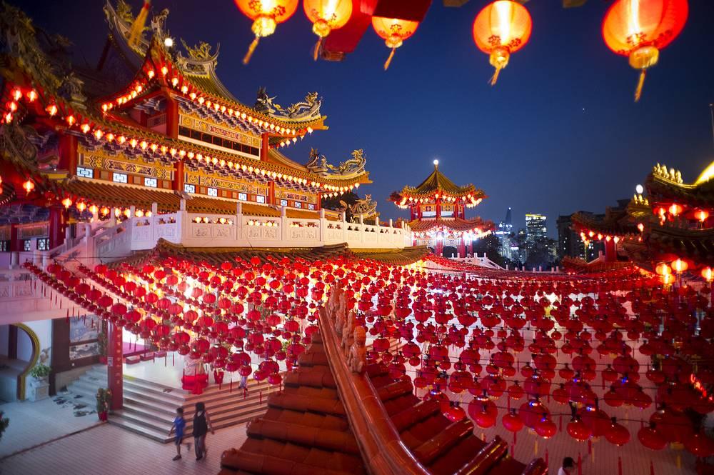 На Новый год улицы городов украшают яркой традиционной атрибутикой преимущественно красного цвета. На фото: новогодние украшения в храме в Куала-Лумпуре
