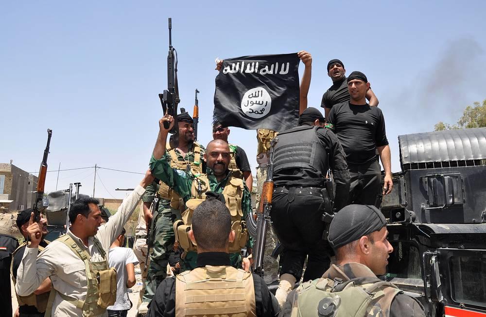 Несмотря на потери в Мосуле и провинции Найнава, иракская армия продолжила сопротивление. На фото: иракские военные с флагом ИГ, захваченным в ходе боев, июнь 2014 г.