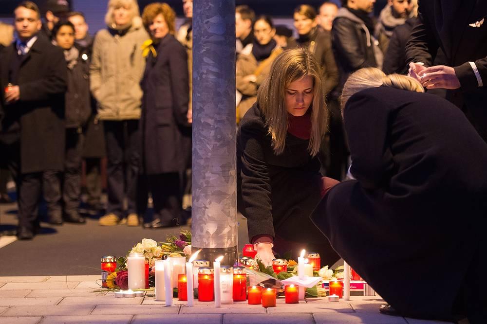 Сотрудники Germanwings и Lufthansa возлагают цветы и устанавливают свечи у здания штаб-квартиры Germanwings в Кельне, Германия