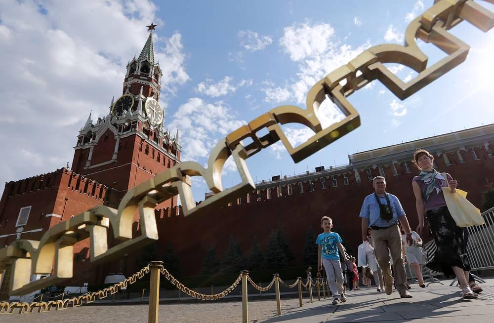Посетители у прохода на Красную площадь, расположенного рядом с воротами Спасской башни Московского Кремля