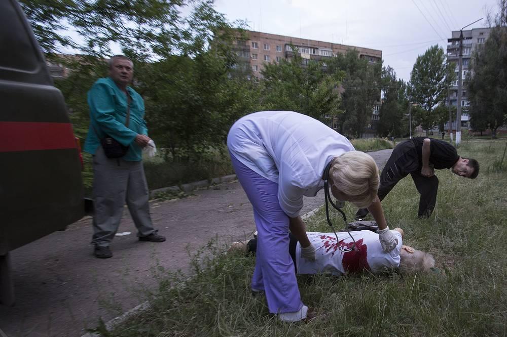 Врачи осматривают тело женщины, погибшей в результате обстрела со стороны киевских военных, Славянск, Донецкая область,  май 2014 года