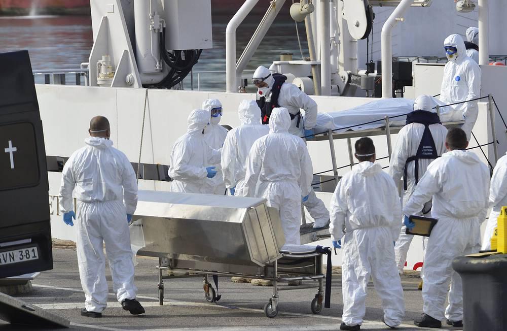 19 апреля в службу береговой охраны Италии поступил сигнал бедствия с судна, направлявшегося из Ливии к югу Апеннин. Сообщалось, что на его борту находятся более 700 человек. На фото: сотрудники береговой охраны Италии доставляют тела погибших на берег, 20 апреля 2015 года
