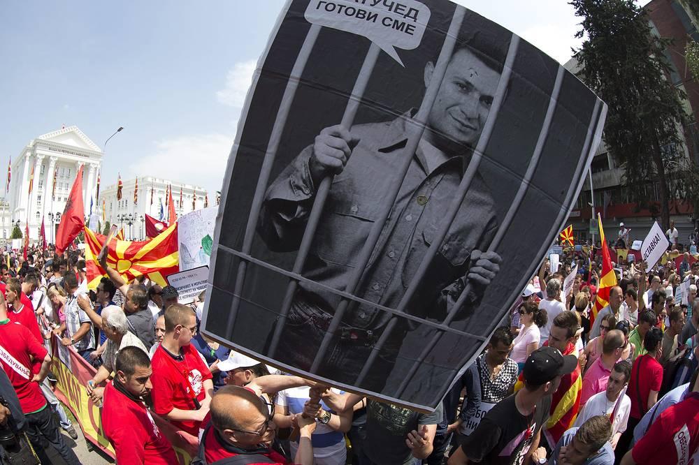 Лидер СДСМ Зоран Заев настаивает на том, что единственным выходом из политического кризиса может быть уход премьера в отставку, формирование переходного правительства и назначение внеочередных выборов в парламент. На фото: плакат с изображением премьер-министра Македонии Николы Груевского за решеткой