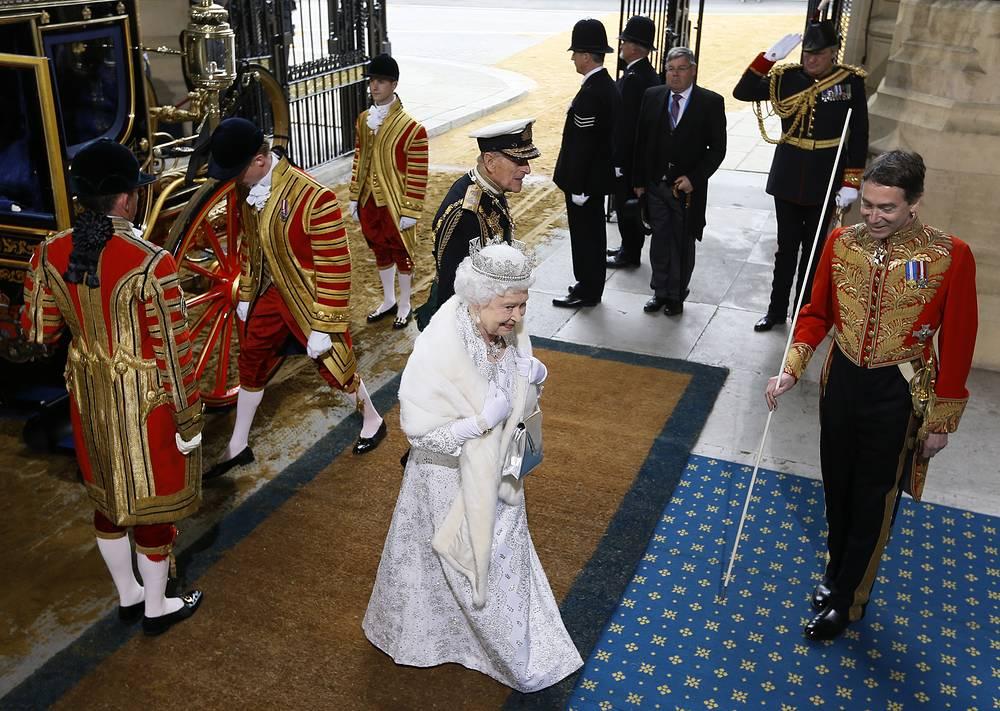 К прибытию королевы на башне Виктории Вестминстерского дворца вместо британского флага поднимается королевский штандарт. На фото: Елизавета II направляется в палату лордов в  Вестминстерском дворце, 2014 год