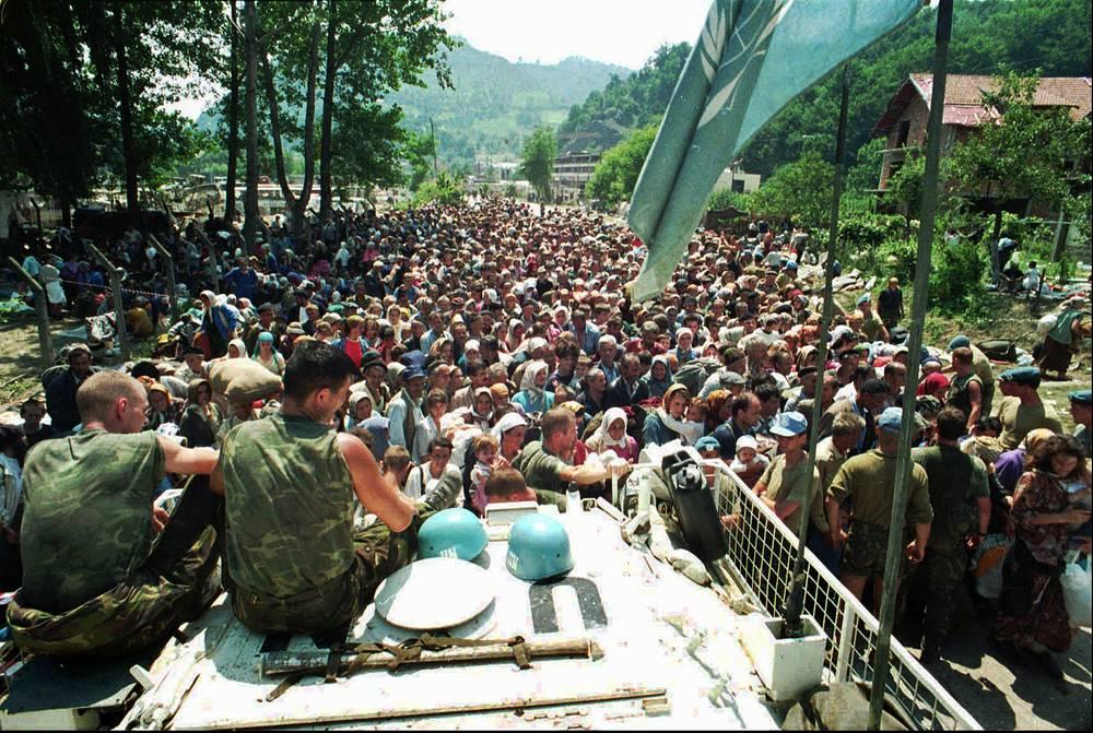 """В 1993 году ООН объявила Сребреницу """"зоной безопасности"""". Организация пыталась не допустить многочисленных жертв среди мирного населения Боснии и Герцеговины. Это привело к тому, что в город прибыли тысячи беженцев. На фото: голландские миротворцы ООН смотрят на мусульманских беженцев из Сребреницы, собравшихся в деревне Потокари (около 5 км к северу от Сребреницы). 13 июля 1995 года"""