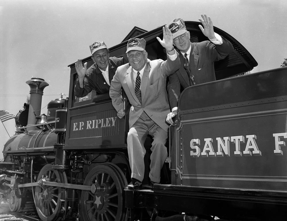 """Парк развлечений окружает железная дорога, которую обслуживают пять старинных паровых локомотивов, три пассажирских поезда и один товарно-пассажирский. На фото: Уолт Дисней, губернатор Калифорнии Гудвин Дж. Найт и глава железной дороги Санта-Фе Фред Г. Герли объезжают """"Диснейленд"""", 17 июля 1955 года"""