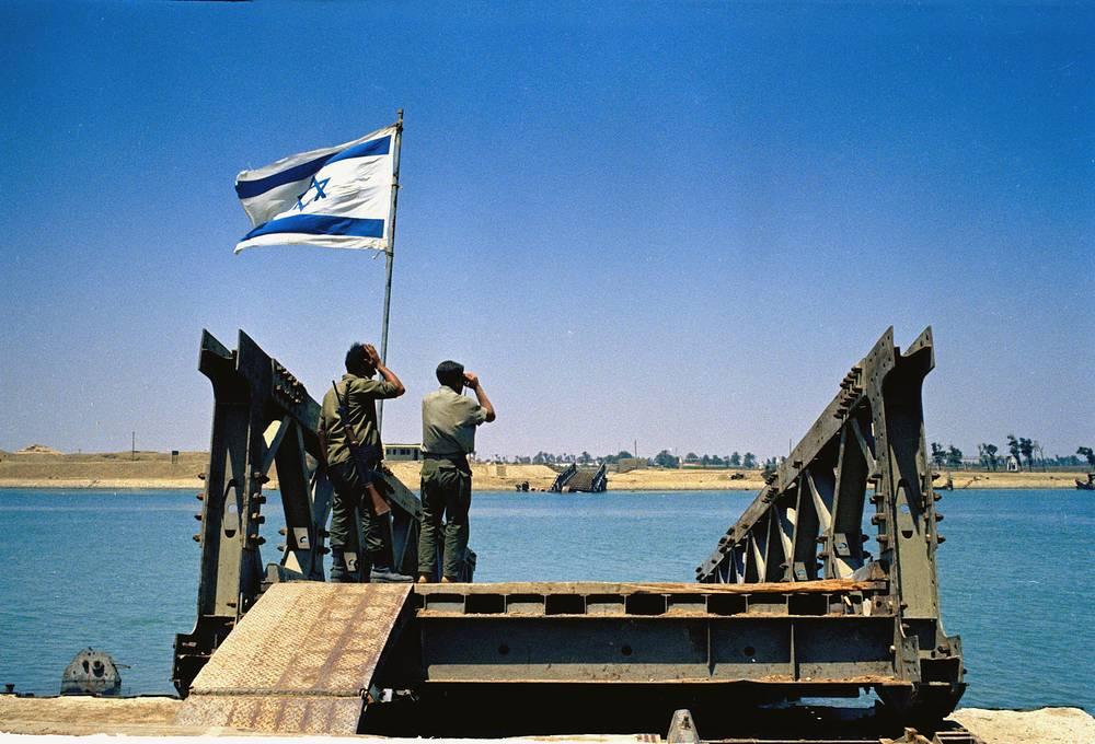 В 1967-1975 гг. канал был закрыт для судоходства из-за арабо-израильских войн. В ходе шестидневной июньской войны 1967 г. Израиль оккупировал Синайский полуостров и занял восточную сторону канала. На фото: израильские солдаты стоят на разрушенном мосту, глядя на египетский берег Суэцкого канала, июнь 1967 года