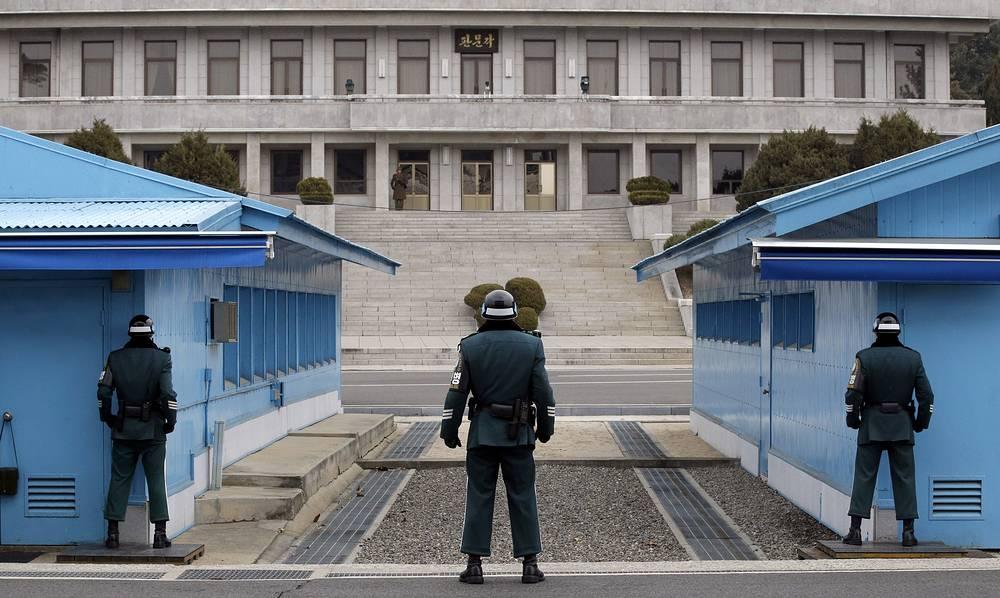 20 августа КНДР обстреляла позиции южнокорейских военных в западной части Демилитаризованной зоны, где размещены громкоговорители, используемые Сеулом в пропагандисткой кампании против Пхеньяна. Южнокорейские военные открыли ответный огонь из артиллерии по району выстрелов со стороны КНДР. На фото: северокорейский солдат (в центре) смотрит в сторону Южной Кореи, Пханмунджом, 2014 год