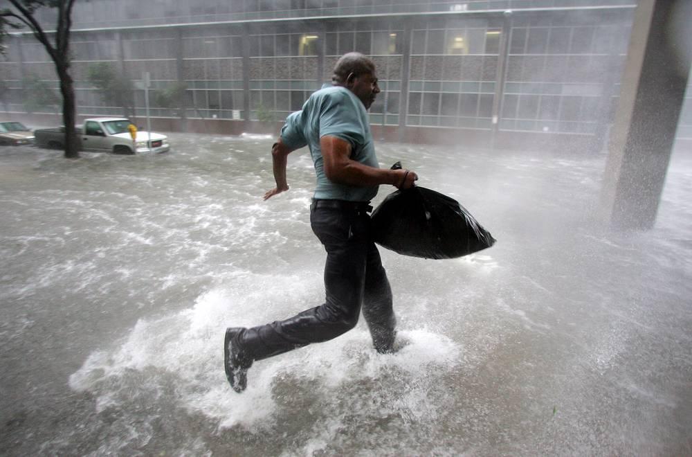 Житель Нового Орлеана Арнольд Джеймс пытается добраться до Луизианского стадиона, 06:00, 29 августа. Крышу его дома сорвало порывом сильного ветра