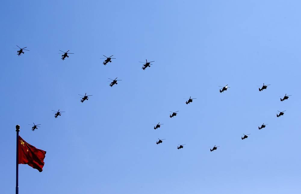 Над площадью пролетели самолеты раннего предупреждения в сопровождении группы истребителей, окрасивших небо в разные цвета, и другие боевые самолеты и вертолеты. На фото: вертолеты китайской армии