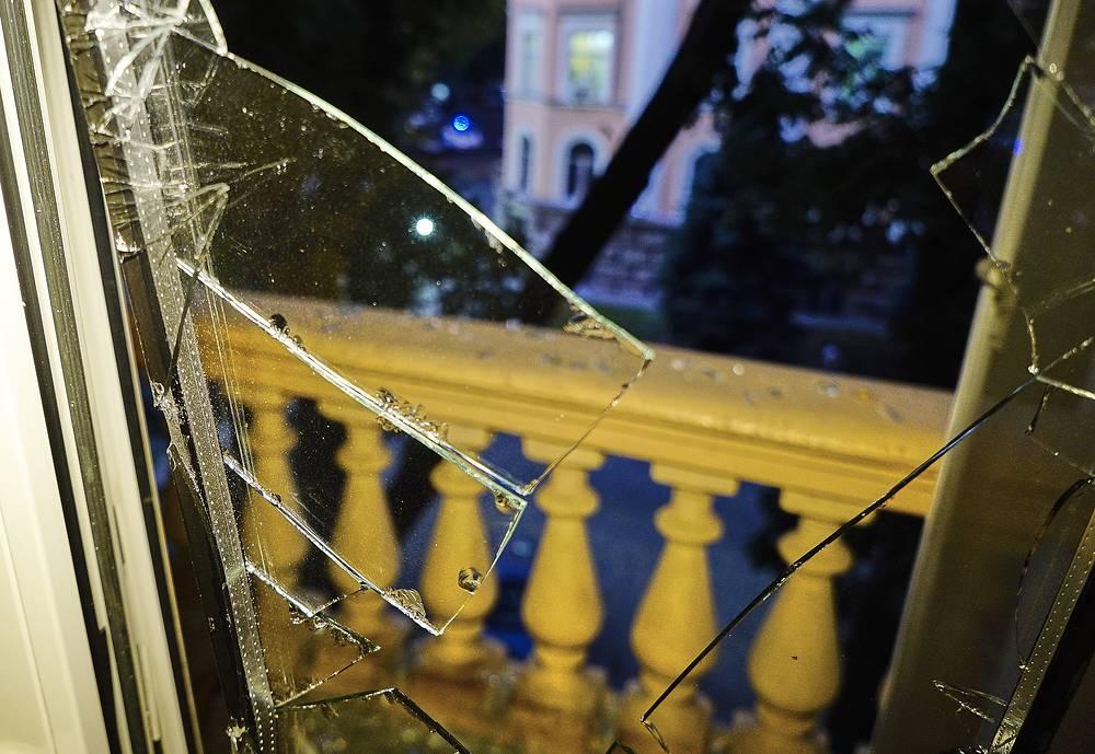 Выбитое стекло в окне жилого дома после взрыва у здания управления Службы безопасности в центре города