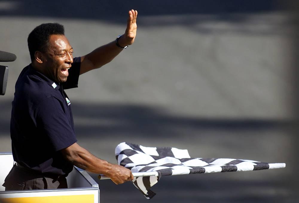 """Пеле посещает не только футбольные матчи. Список его увлечений очень широк (На фото: экс-нападающий с флагом во время Гран-при Бразилии """"Формулы-1"""")"""
