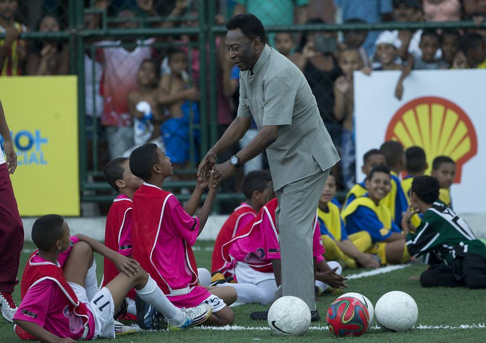 Встреча Пеле с детьми на церемонии открытия футбольного поля, которое обрабатывает кинетическую энергию во время матчей (общедоступная площадка была построена при участии легенды футбола и компании Royal Dutch Shell)