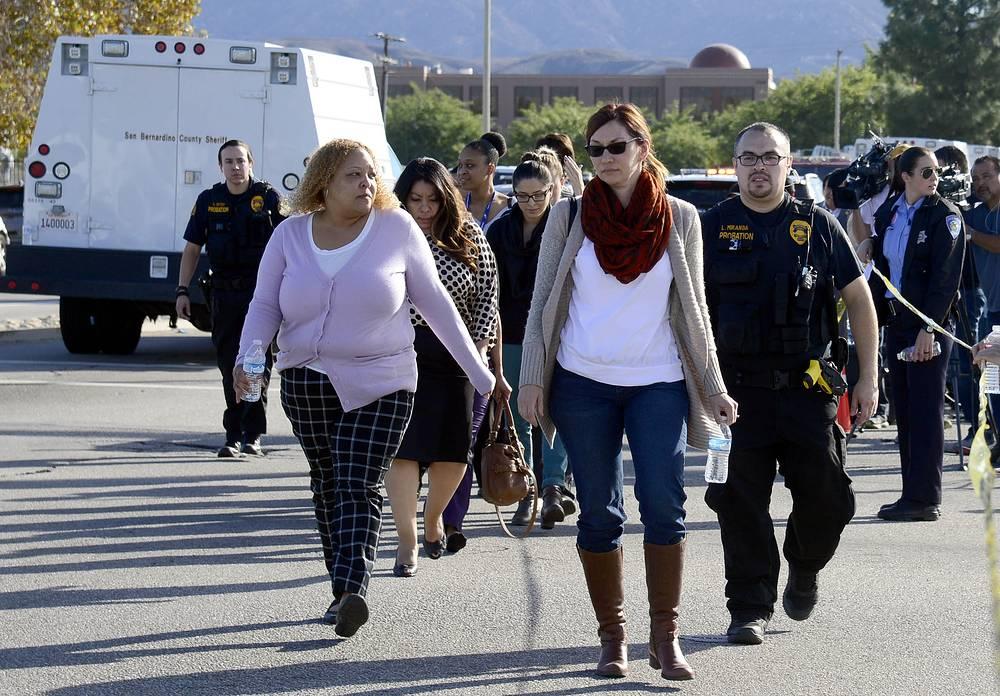 Сотрудник полиции сопровождает эвакуированных людей с места перестрелки в центре помощи людям с ограниченными возможностями в Сан-Бернардино, Калифорния, 3 декабря