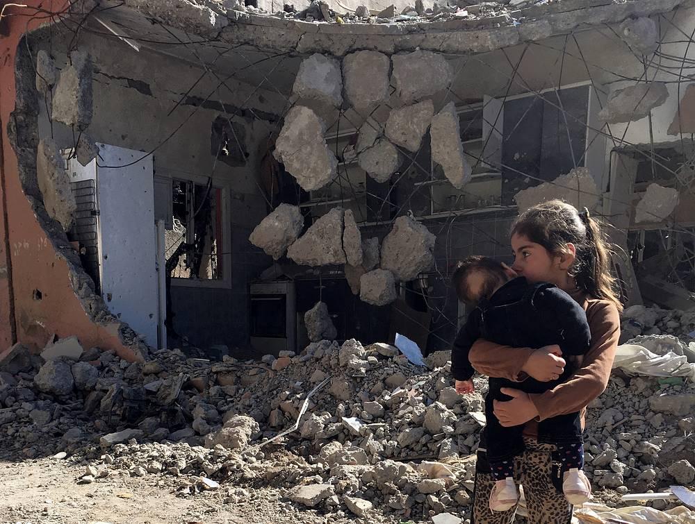 Девочка держит на руках ребенка перед разрушенным домом в Джизре, Турция, 2 марта