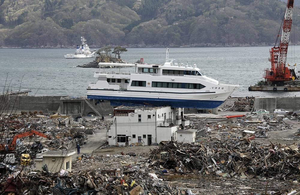 Туристическое судно, заброшенное во время цунами на крышу гостиницы в Оцучи, северная Япония, 07 мая 2011 года