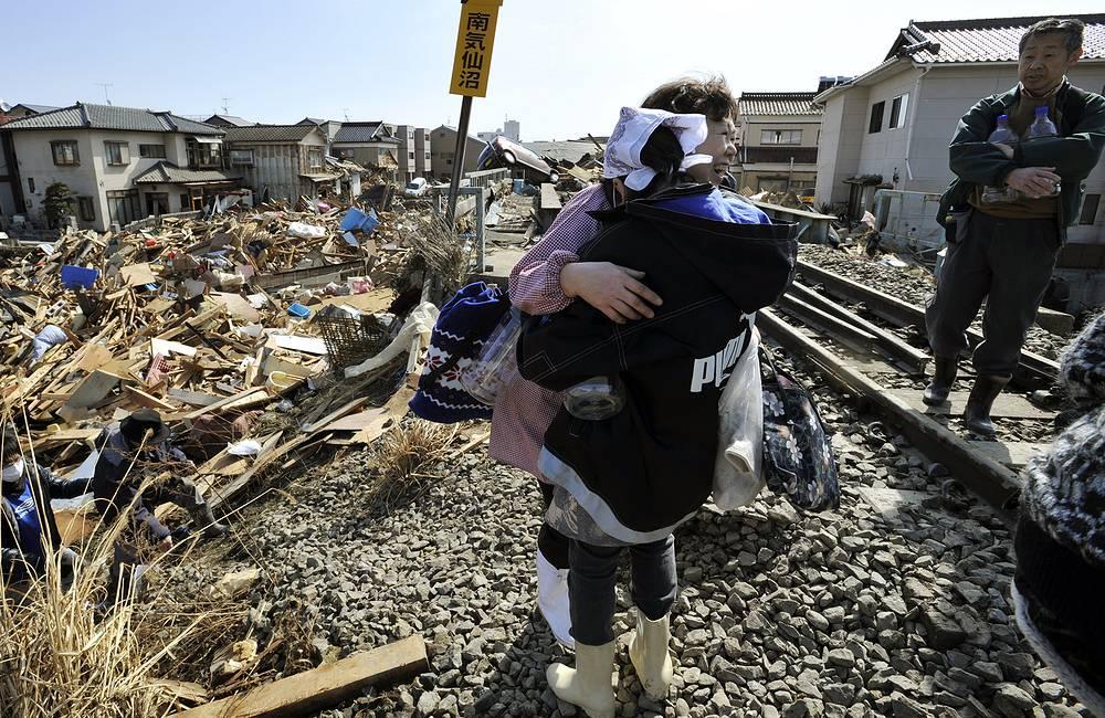 Выжившие после цунами обнимают друг друга, Кесеннума, префектура Мияги, северная Япония, 14 марта 2011 года