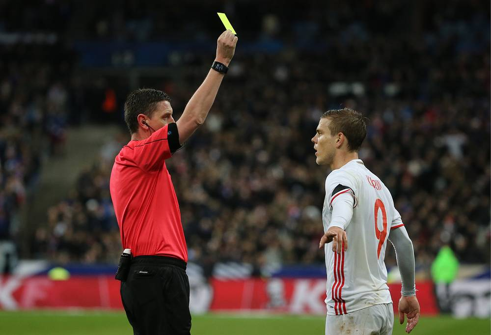 Шотландский арбитр Крэйг Томпсон показывает желтую карточку нападающему сборной России Александру Кокорину