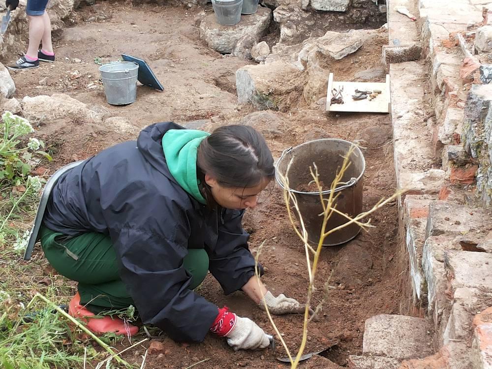Молодые археологи наполняют ведра землей XII века